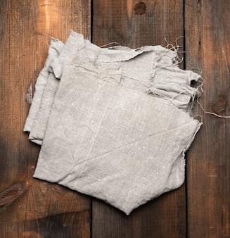 Серое кухонное полотенце на коричневой деревянной поверхности, вид сверху, копия пространства