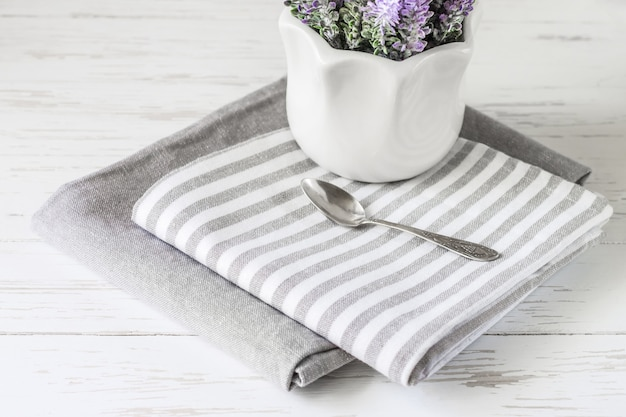 Gray kitchen towels on a white wooden table with flowers