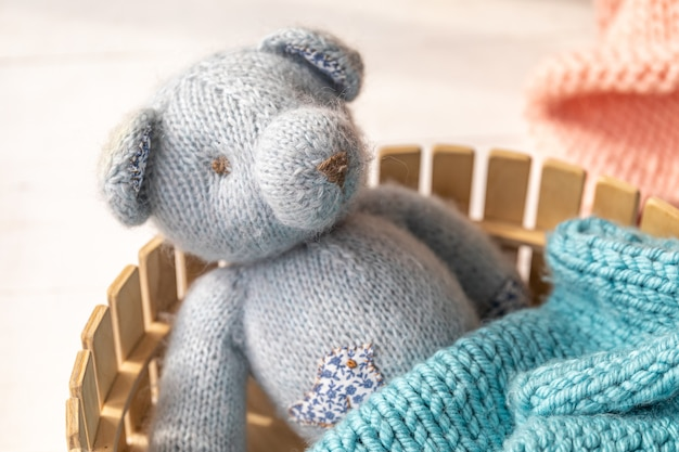A gray knitted bear is lying in a small wooden basket, covered with a knitted blanket. concept of children's sleep