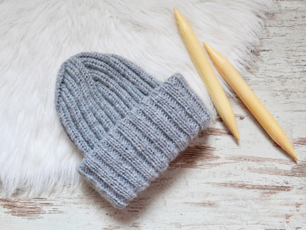 Gray knitted hat on white fur
