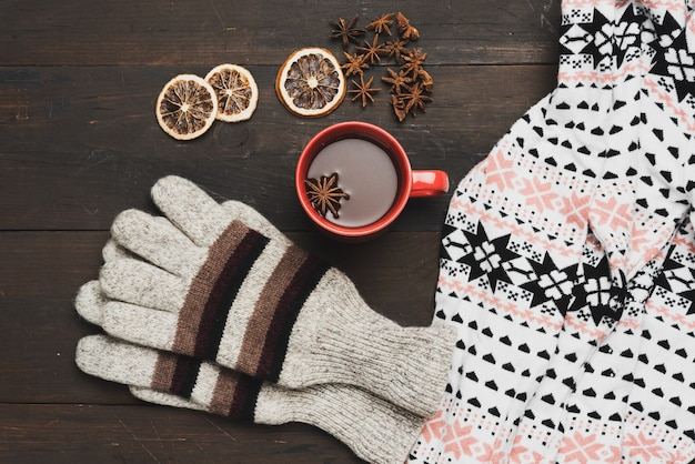 Gray knitted mittens and red cup with a drink on a brown wooden table, top view