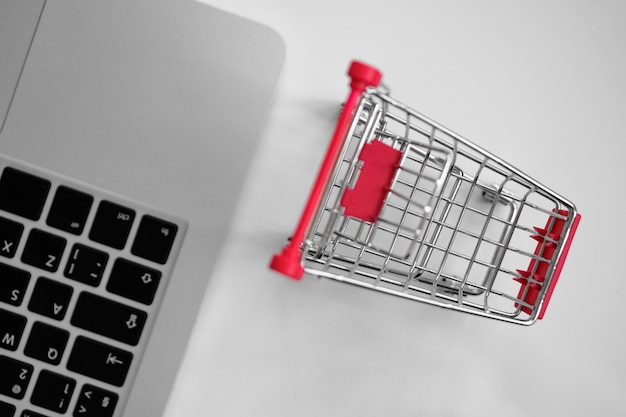 A gray laptop on a table next to a shopping cart from a supermarket. top view.