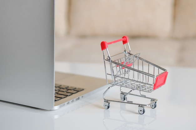 A gray laptop on a table next to a shopping cart from a supermarket.