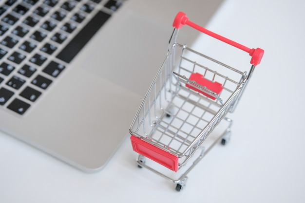 A gray laptop on a table next to a supermarket trolley. the  of shopping for products on the internet.