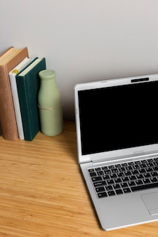 Gray laptop with books on wood desk