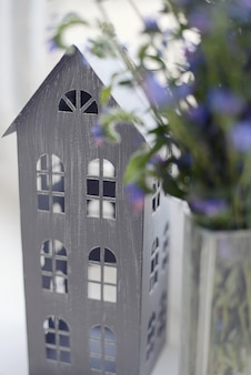 Gray layout of the house stands next to the blue flowers on the windowsill indoors