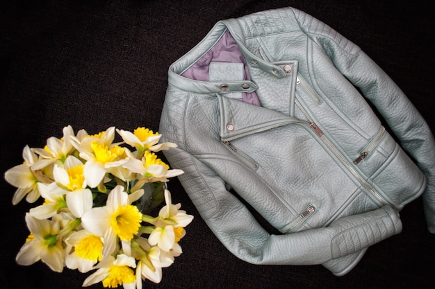 Gray leather jacket and a bouquet of daffodils.