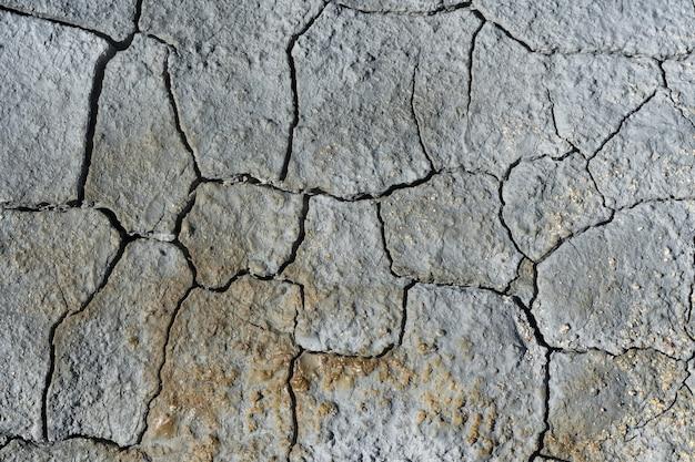 Серая светло-голубая сухая потрескавшаяся поверхность вулканической земли превратилась в пустыню. естественный фон или текстура в кратере действующего вулкана. понятие: глобальное потепление, засуха, эрозия почв.
