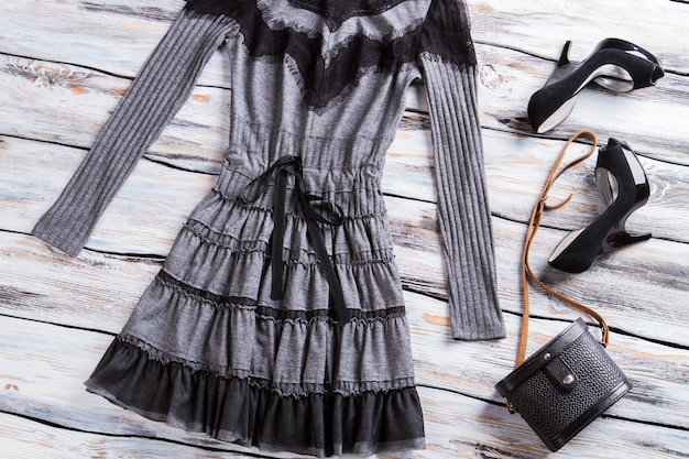 Gray long sleeve dress. gray dress on wooden background. luxury heel shoes in boutique. girl's dark outfit for parties.