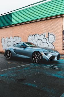 Gray luxury car parked beside wall with graffiti