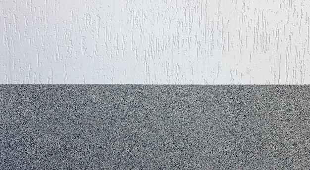 Gray marble chips and decorative light stucco on the wall divided by a horizontal line. building facade background. stucco texture on the street.