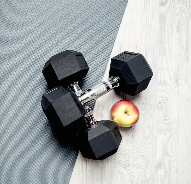 灰色のマット、2つの黒いダンベル、リンゴ