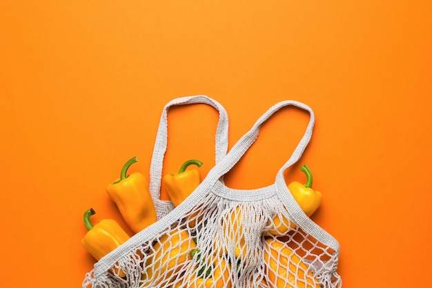 Серый сетчатый мешок со спелым болгарским перцем на оранжевом фоне. вегетарианская пища.