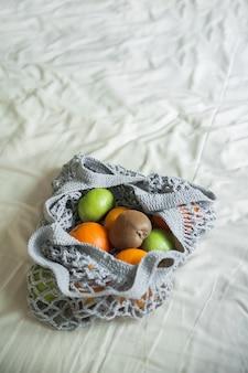 Серая сетчатая сумка с крупным планом желтых апельсинов и копией пространства. эко-сумка ручной работы на текстиле