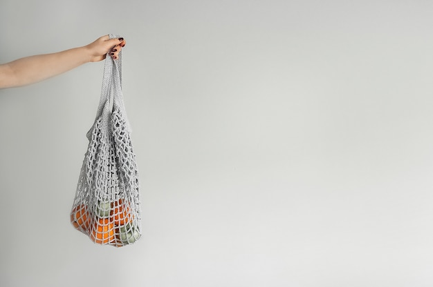 Gray mesh bag with yellow oranges close-up and copy space. handmade eco bag in hand