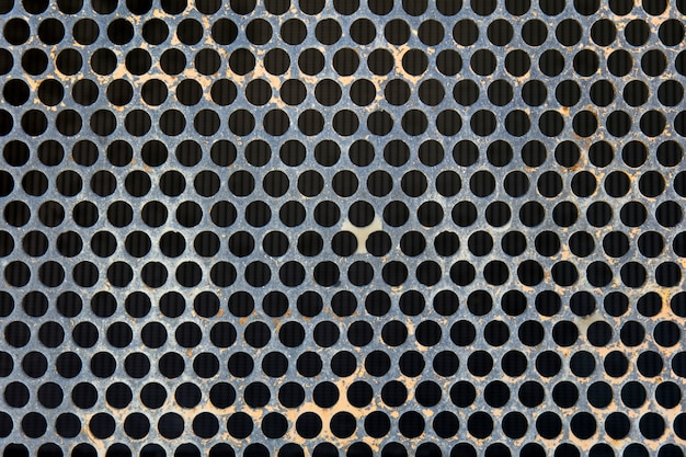 Gray metal surface with black round holes