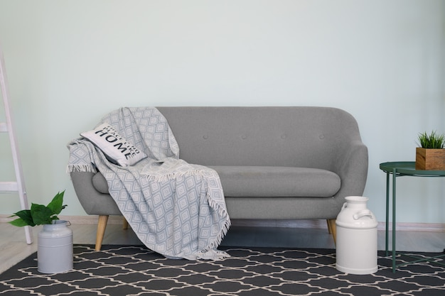 Gray modern couch with cushion and blanket and black carpet