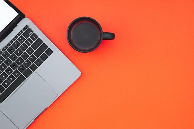 빨간 표면에 회색 현대 노트북 및 음료 컵