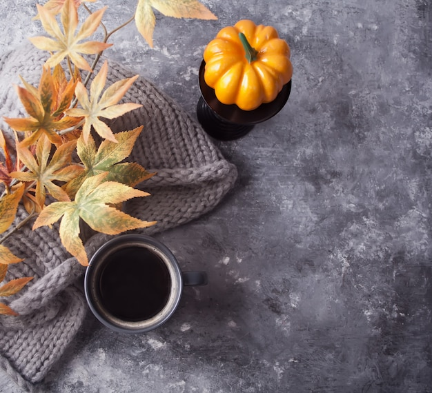 Gray mug of coffee, autumn leaves, pampkin and scarf on gray table. autumn concept. minimalism