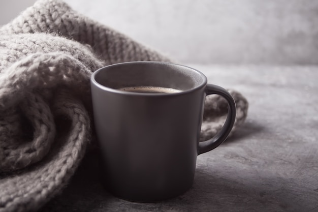 Gray mug of coffee and gray scarf on the gray table