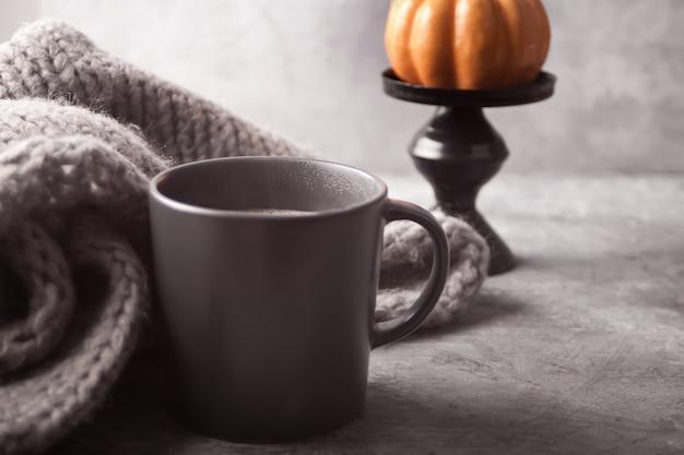 Gray mug of coffee with pumpkin and gray scarf on the gray table
