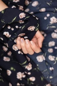 Серый дизайн ногтей. женская рука с блеском маникюра.