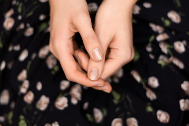 Design delle unghie grigio. mano femminile con manicure glitterata.