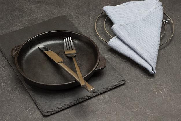 テーブルの上の灰色のナプキン。空の鋳鉄フライパンにスプーンとフォークを入れます。黒の背景。上面図