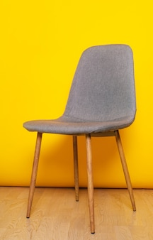 Gray office chair standing isolated on the background of yellow wall