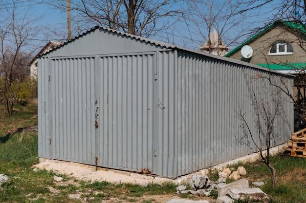 Серый старый металлический гараж для машины, стоящий на заднем дворе
