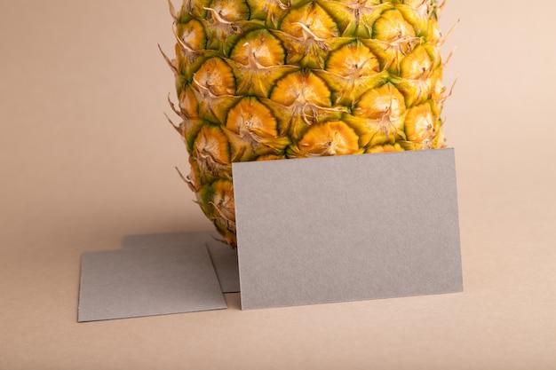 오렌지 파스텔 배경에 잘 익은 파인애플이 있는 회색 종이 명함. 측면 보기, 복사 공간입니다.