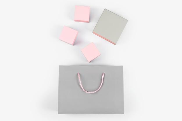 Серая бумажная хозяйственная сумка и розовые подарочные коробки на светлом фоне. свободное место для текста. шоппинг, продажа, сюрприз или концепция подарка.