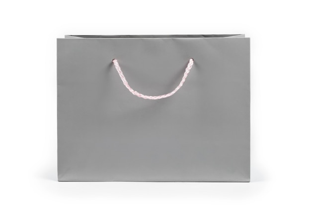 Серая бумажная хозяйственная сумка на светлом фоне. свободное место для текста. шоппинг, продажа, сюрприз или концепция подарка.