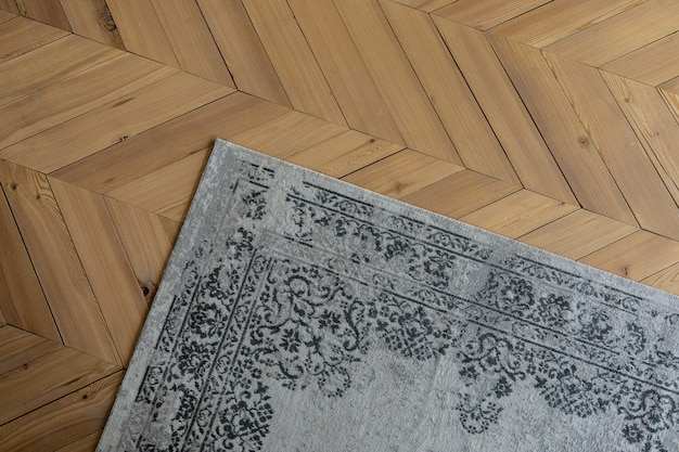 灰色の模様のカーペットは木の床にあります