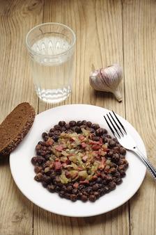 Серый горошек с колбасой, беконом и луком на деревянном столе