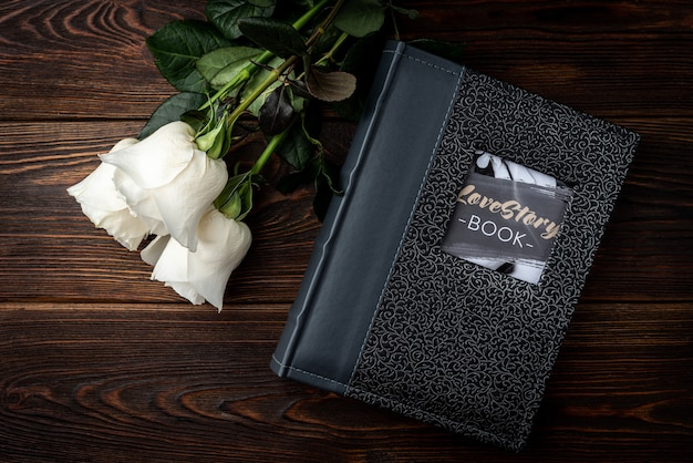 Gray photo album and white roses on dark wooden table.