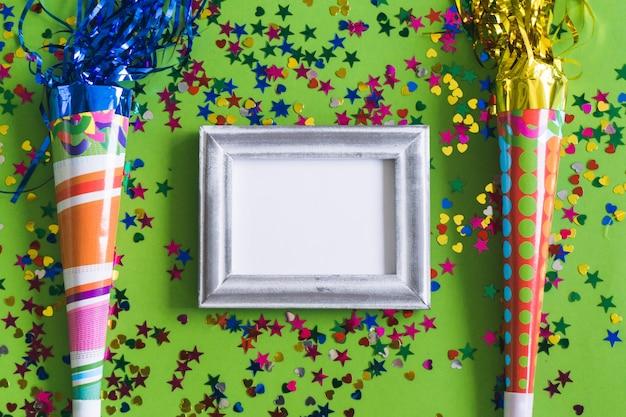 Cornice grigia con confetti colorati e trombe
