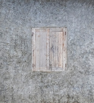 Серая штукатурка стены со старым винтажным окном