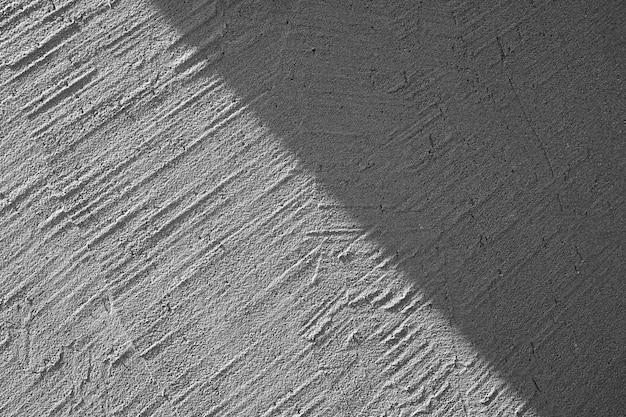 影のテクスチャの背景を持つ灰色の漆喰壁