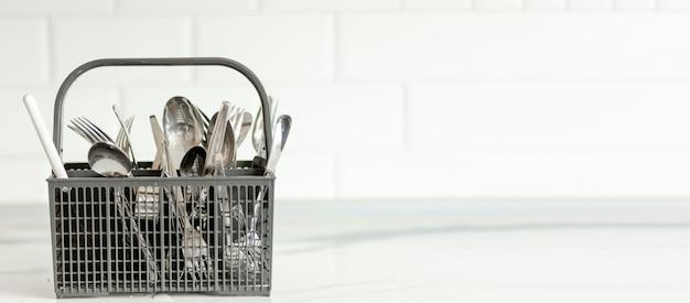 白い背景の上のフォーク、スプーン、ナイフと食器洗い機用の灰色のプラスチック製カトラリーバスケット