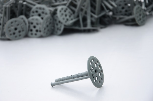 A gray plastic dowel (fastening) for thermal insulation with round umbrella caps lies on a gray foam polystyrene plate