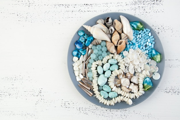 Gray plate with beads and seashells