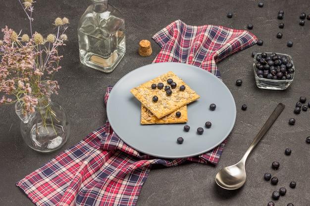 市松模様のナプキンにクッキーとブルーベリーが入ったグレーのプレート。ボトルウォーター。ガラスのボウルにブルーベリー。スプーンはテーブルの上にあります。黒の背景。上面図