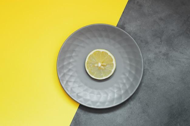 노란색 배경에 레몬이 있는 회색 접시입니다. 트렌드 컬러 2021 - 궁극의 회색과 조명.