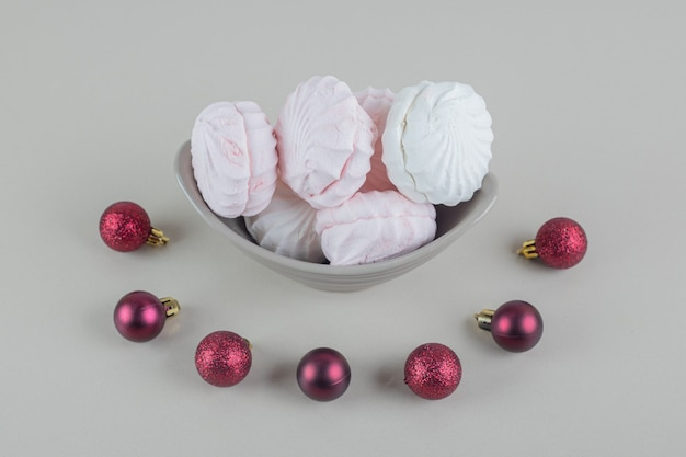 A gray plate with vanilla and pink zephyrs with christmas balls.