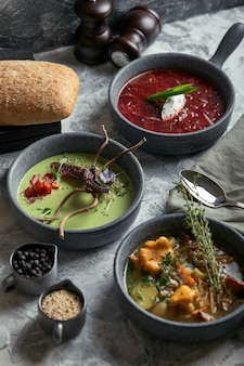 Gray plates with different soups on a gray . plate with asparagus soup with octopus, a plate of traditional borscht with sour cream, a plate with mushroom soup and standing on multi-colored