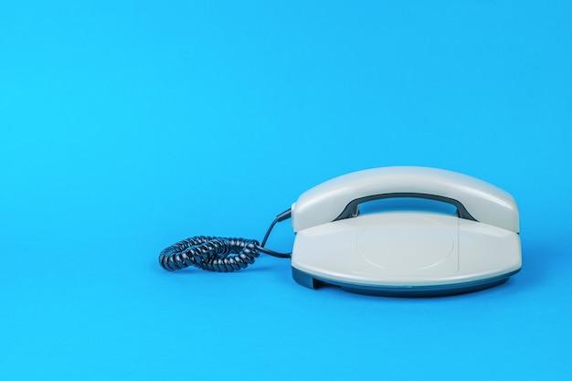 青の背景に灰色のレトロな電話。テキスト用のスペース。