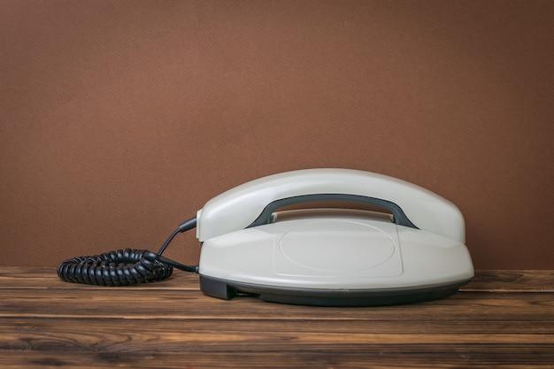 茶色の背景に木製のテーブルの上の灰色のレトロな電話。レトロなコミュニケーション手段。