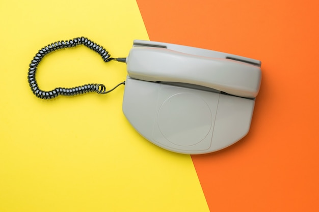 A gray retro phone on a two-tone orange and yellow background. flat lay.