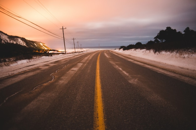 Серая дорога возле поля, покрытая снегом под бело-оранжевым небом